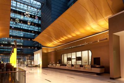 Weit aufschwingende Flügel akzentuieren die Rezeption im luftigen Atrium der großen Hotel-Lobby. Ergänzt wird die empfangende Geste durch golden schimmernde Rückwände, beschichtet mit Capadecor Metallocryl / Foto: JOI-Design, Hamburg