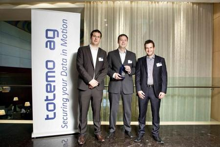 "Robert A. Bertschinger, VP Sales & Alliances Totemo (li.), und Claudio Pettannice, Channel Manager Totemo (re.), überreichen Mario Emig, Head of Information Security, Business Development bei Controlware, den Award ""TrustDEX Business Partner of the Year 2011"""