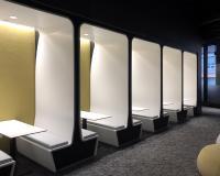 """Die sogenannten """"nooks"""" reihen sich vor einem dunklen Hintergrund aneinander und treten dank der hell beleuchteten Innenverkleidung und Sitzflächen deutlich hervor."""