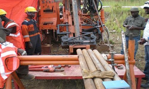 Arbeiter und Bohrhülsen auf Manono; Foto: AVZ Minerals