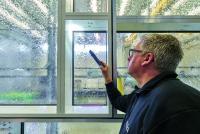 An der Innenseite wird kontrolliert, ob bei dem Test auf Schlagregendichtigkeit Feuchtigkeit durch die Fugen der Schüco AF UDC 80 Fassadenelemente getreten ist / Bildnachweis: Christian Eblenkamp