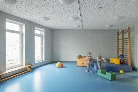 Viel Platz zum Toben haben die Kinder im Bewegungsraum mit dem blauen Schwingboden. Für Farbakzente vor der grauen Wand sorgen die bunten Polster und Kissen. (Foto: Caparol Farben Lacke Bautenschutz/Martin Duckek)