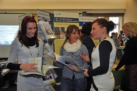 Die Studentinnen Franziska Dose (li.) und Sarah Smolinski lassen sich von Birgit Ferner (re.) über die Weiterbildungsangebote der IHK-Bildungsakademie (IBA) informieren (Quelle: IHK Magdeburg)