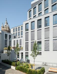 Die ruhige Hofseite mit Begrünung, Terrassen und Skyline-Blick bietet einige der attraktivsten Wohnungen inmitten der Frankfurter Innenstadt (Fenstersysteme: Schüco AWS 75.SI). Bild: Schüco International KG  / Fotograf: Stefan Schilling