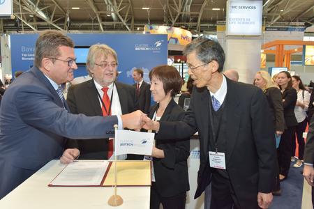 Bayerischer Staatssektretär Franz Josef Pschierer, Prof. Dr. Horst Domdey bei der Vertragsunterzeichnung am bayerischen Gemeinschaftsstand auf der BIO-Europe 2015