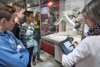 Im Ausstellungsfahrzeug können Schülerinnen und Schüler einen kleinen Industrieroboter programmieren, um ihn mittels Koordinateneingabe zu vorgegebenen Markierungen zu lotsen. Dabei zeigt sich, wie viel Mathematik und Informatik in den künstlichen Helfern steckt