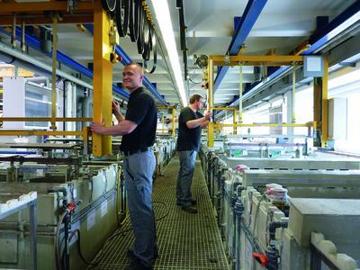 Florian Kasper (l.) und Kassian Bartolf (r.) bedienen die Trommelanlage, in der u.a. 2 Tonnen Zinkdruckguss pro Tag beschichtet werden.