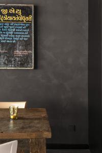 Eichenholzmöbel bilden einen warmtonigen Kontrast zu den dunklen Wänden. Ein Hingucker sind die drei indisch beschrifteten Tafeln. Sie stammen von einer Universität – auf der Rückseite könnten die Barbesucher sogar die englische Übersetzung lesen / Fotos: Caparol Farben Lacke Bautenschutz/Blitzwerk.de, Marek Lufft
