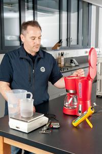 Für ein Urteil über die Gebrauchstauglichkeit einer Kaffeemaschine wird auch die Durchlaufzeit und die Brühtemperatur gemessen. Dabei sind die Mengen von Kaffeepulver und Wasser für den Testbetrieb vorgegeben. TÜV SÜD-Experte Christian Kästl bereitet den Test vor