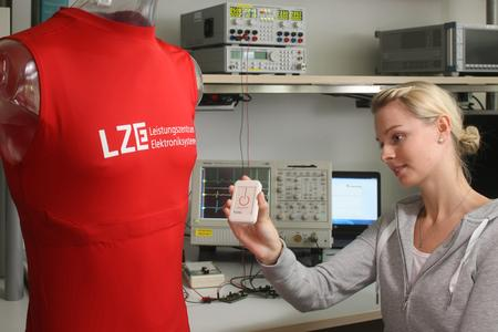 FitnessSHIRT (left) with integrated electrodes and a respiratory band to measure a single-channel-ECG and the respiratory rate. Measured data are collected on a technical unit (in model's hand; clipped on the back of the shirt during activity) and sent via Bluetooth to a smartphone or tablet. (Photo: Kurt Fuchs / Fraunhofer IIS)