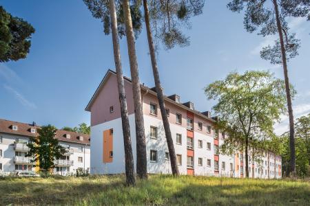 Harmonisch fügen sich die neuen Fassadenfarben in das natürliche grüne Umfeld ein – schöne Blickachsen entstehen. Der Baumbestand wurde in das neue Quartierskonzept integriert (Foto: Caparol Farben Lacke Bautenschutz/blitzwerk.de)