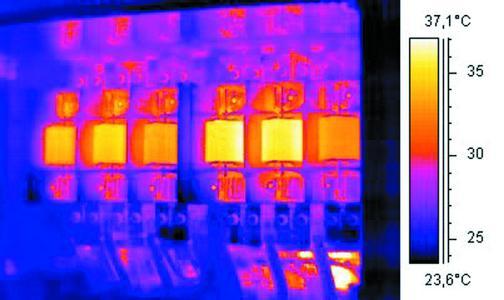 Während im Digitalbild keine Unterschiede der Bauelemente erkennbar sind, deutet das IR-Bild durch die Darstellung unterschiedlicher Temperaturen auf eine erhöhte Belastung bzw. fortgeschrittenere Alterung von zwei Bauteilen hin