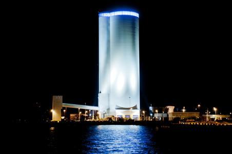 Skylinie des Mehrkammersilos bei Nacht mit Schiffsentladestation und Becherwerksturm