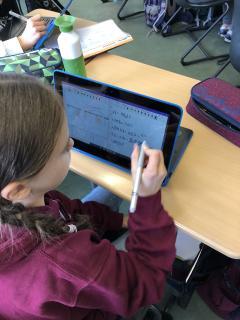 Schülerin schreibt auf dem Display ihres Laptops