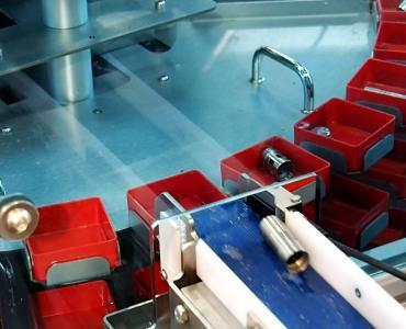 Teile werden über ein Zuführband in den Kästchen abgelegt