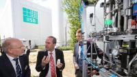 Bayerns Wirtschaftsminister und Stellvertetender Ministerpräsident Hubert Aiwanger (Mitte), der kommissarische Leiter des Fraunhofer IISB Prof. Martin März (links) und   IISB-Wissenschaftler Johannes Geiling diskutieren Aspekte der Langzeitspeicherung von regenerativ erzeugter Energie mittels Wasserstoff und organischer Trägerflüssigkeiten   (LOHC).