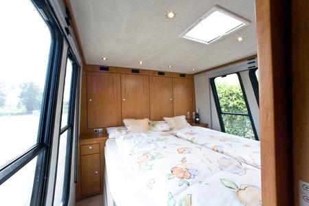 The both side easy entry queen-size bed under which a Smart for two parked in a car garage