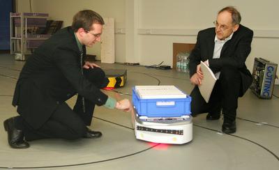 """Dr. Sebastian Behling (links) und Hans-Heinrich Götting mit """"KATE"""". Die """"kleine automatische Transport-Einheit"""" wurde von der Lehrter Firma Götting entwickelt. Im Forschungsprojekt """"FTF out of the box"""" soll sie Sehen, Hören und Denken lernen. (Foto: Susann Reichert / IPH)"""