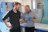 Patrick Streuper (li) und Kai-Uwe Petersmeier mit einem Schachtelprodukt aus dem Kolbus Magenteinleger Typ SW.M 400.