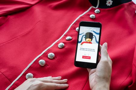 Hand spielt App DataDuell auf der Jacke eines Guards 2/2