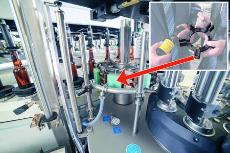 Blick in eine Etikettiermaschine. Im Hintergrund ist der sich drehende Behältertisch zu sehen, auf dem Flaschen zwischen Behälterteller und Zentrierglocken fest eingespannt und zentriert sind. Gummierte Beleimungspaletten (rechts) übergeben die Etiketten an die Greiferzylinder mit der hellgrünen Aufnahmefläche (Mitte). Diese wiederum setzen die Etiketten auf die Behälter auf. Dazu fahren Schieber aus der dahinter verborgenen Schieberführung (oben rechts im kleinen Foto) ein und aus.