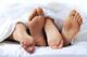 Close-up of the feet of a couple on the bed - togethermedien.net
