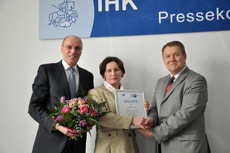 Rolf Lay (links), Vizepräsident der IHK Magdeburg und Wolfgang März, Hauptgeschäftsführer der IHK Magdeburg überreichen Ludmilla Seel die offizielle Urkunde zum Bescheid im Rahmen einer Pressekonferenz am 21. Februar 2013
