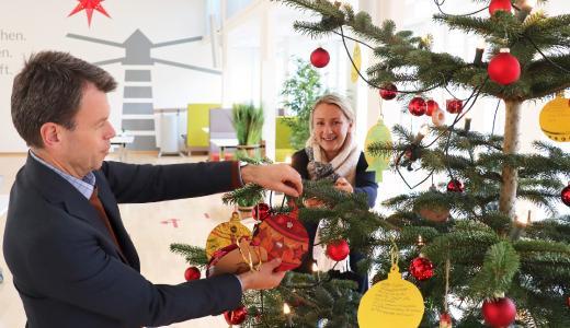 WEMAG-Vorstand Caspar Baumgart und Demmlerhaus-Leiterin Carolin Schulz bringen die Karten mit den Wünschen der Kinder am Weihnachtsbaum im WEMAG-Speisesaal an / Foto: WEMAG/Nele Reiber