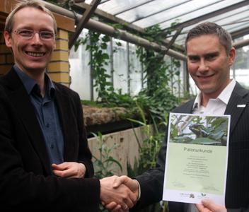 Tobias Ambrosch (re. im Bild) erhält die Patenschafts-Urkunde von Dr. Martins (li. im Bild)