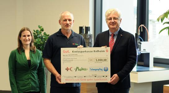 Gründer und Vorstandsvorsitzender Erich Scheugenpflug (rechts) und Karin Prechtner (Marketing, links) überreichen Erich Stauber, dem Projektleiter von MONA (Mitte), den Spendenscheck über 5.000 Euro.