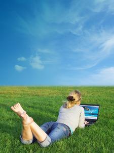 Frau mit PCTV Nano Stick am Laptop auf Wiese
