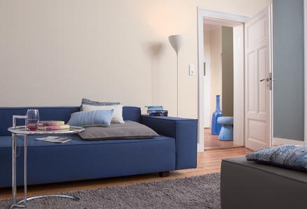 Das warme, helle Beige der Wände und ein ruhiges, kühles Blau als Ergänzung verleihen dem Raum eine erholsame Grundstimmung. Das blaue Sofa greift diese Schwingung auf und gibt – ganz entspannt – eine elegante Note dazu.  Foto: Caparol Farben Lacke Bautenschutz