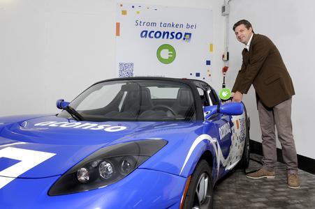 """Stromtankstelle von aconso in Bielefeld: Vorstand Olaf Harms beim """"Betanken"""" des Tesla Roadster von aconso. Die Stromtankstelle steht für jedermann kostenfrei bereit"""