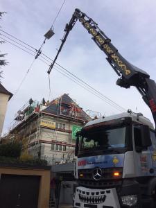 Knifflig: Per Kran wurde das Premium Balkonausstiegsfenster über die Oberleitungen zum Dach transportiert / Foto: LiDEKO