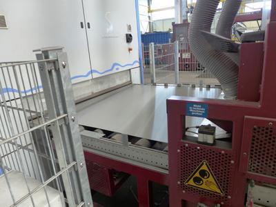 Bild 4: Auf dem Weg zum Schleifen richten seitliche Rollen die Bleche so aus, dass sie genau positioniert in die Schleifmaschine einlaufen