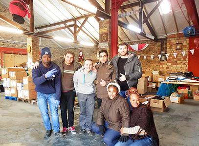 Gemeinsam mit Flüchtlingen helfen die Alpensped-Mitarbeiter Kenan Ramani und Jens Schnöde bei der Kleidersortierung im Benjamin-Franklin-Village.