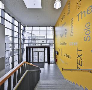 Integrierte Gesamtschule Kaufungen: Die markante, gelbe Wand erscheint wie ein Gesamtkunstwerk. Bei Dunkelheit strahlt die Farbe schon von außen einladend durch die Glasfront.