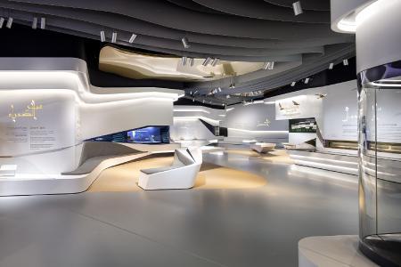 Die Ausstellungsräume der Gallery 4 sind durch eine geschwungene Wandverkleidung aus großflächigen Mineralwerkstoffbändern miteinander verbunden.