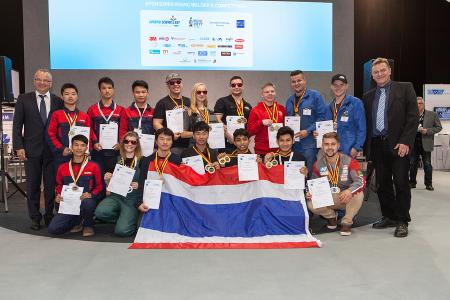"Team Thailand (front) won the ""International Competition"". Team China (left), Team Germany (centre) and Team Europe (right) expressed their congratulations, as did Dr.-Ing. Roland Boecking (DVS General Manager, far left) and Prof. Dr.-Ing. Heinrich Flegel (DVS President, far right) / Photo: DVS / Alexander Sucrow Fotografie"