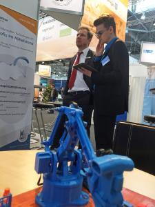 Tim Möckel erklärt Christoph Neuberg, Geschäftsführer Industrie/Außenwirtschaft der IHK Chemnitz, das Ressourcen-Cockpit MARCO über einen Monitor.
