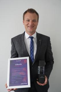 """HARTING Automotive Managing Director Marco Grinblats beams after Harting Automotive received the Volkswagen Group Award 2020 in the """"E-Mobility"""" category"""