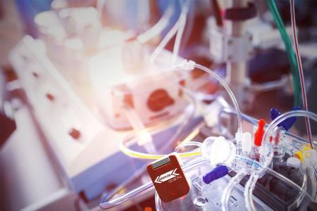 Nicht-invasiver Durchfluss- und Blasensensor SONOFLOW® CO.56 Pro zur kombinierten Flow-Bubble Messung freihängend an einer Herz-Lungen-Maschine / Bildkomposition: SONOTEC, Adobe Stock