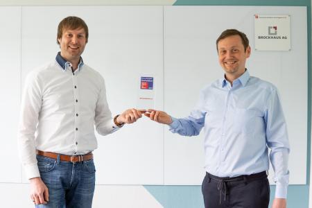 Guido Nippe, Head of IT Consulting und Matthias Besenfelder, Vorstand (v. l. n.) mit der Great Place to Work® Trophäe