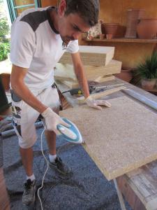 Mit dem Bügeleisen werden die Schnittflächen der Hanfplatten CapaCoustic Nature durch überbügeln nachgeglättet. Die Platten lassen sich mit der Stichsäge mit einem Dämmstoffsägeblatt schneiden, die Fase wird mit einem Handwinkelschleifer herausgearbeitet (Foto: Bernd Schamberger/Caparol)