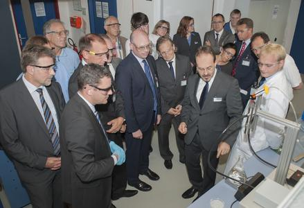 Wolfgang Lorscheider, Technical Manager of Dymax Europe GmbH, shows Sven Gerich, Lord Major of Wiesbaden, and the other visitors, applications of light curable adhesives during the inauguration event.