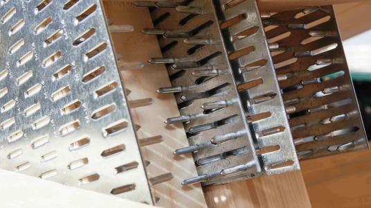 Metall verbindet Holz: Nagelplatten sind weltweit bewährte Holzverbindungsmittel, die an Knotenpunkten beidseits in zwei stumpf stoßende Holzstäbe gepresst werden, so dass eine dauerhaft belastbare Verbindung entsteht. Je nach statischen Erfordernissen unterscheiden sich die metallischen Platten in ihrer Größe und Dicke, der Anzahl der ausgestanzten Nägel sowie der Art des Metalls. (Foto: Krug/GIN, Ostfildern; www.nagelplatten.de)
