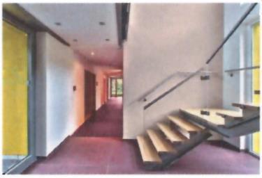 Ein roter Flur verbindet den Altbau mit dem Neubau (unser Bild). Die hellen Wände (Palazzo 30 und Palazzo 50) scheinen warm angestrahlt zu sein - das ist aber nur eine - willkommene - Reflektion des dunkelroten Bodens / Foto: Caparol
