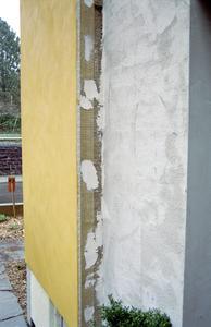 Die Detailaufnahme neben der Eingangstür zeigt die Ausführung der Fassadendämmung kurz vor Abschluss der Arbeiten.