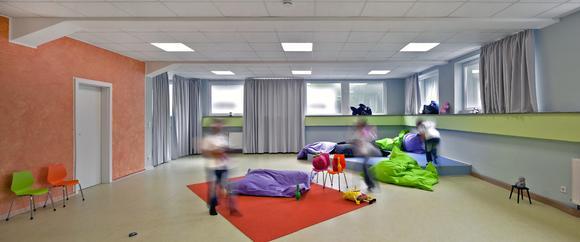 Der Farbbereich Grün-Blau im Help & Hope Kidstreff wird ergänzt durch warme Gelb-Orangetöne als Ausgleich, wie hier im großen Spielzimmer. Die Farb- und Materialzusammenstellungen für Wände und Bodenflächen sind speziell auf die Altersstufe der Nutzer sowie auf unterschiedliche Raumfunktionen und Verweilzeiten abgestimmt, (Foto: Caparol/Help & Hope)