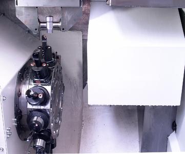Bearbeitung von T-Stücken auf einer DVH 250 mit 12-fach Werkzeugrevolver. Rechts daneben vor Spänen und Kühlmittel geschützt die Wendestation